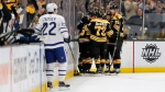 Boston Bruins players surround teammate Charlie Coyle after he scored a goal as Toronto Maple Leafs defenseman Nikita Zaitsev (22) looks on during the first period of Game 2 of an NHL hockey first-round playoff series, Saturday, April 13, 2019, in Boston. (AP Photo/Mary Schwalm)