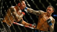 Dustin Poirier, right, punches Max Holloway during an interim lightweight title mixed martial arts bout at UFC 236 in Atlanta, early Sunday, April 14, 2019. (AP Photo/Michael Zarrilli)