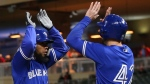 Toronto Blue Jays' Teoscar Hernandez, left, celebrates his go-ahead three-run home run off Minnesota Twins' pitcher Adalberto Mejia with Justin Smoak in the eighth inning of a baseball game Monday, April 15, 2019, in Minneapolis. (AP Photo/Jim Mone)