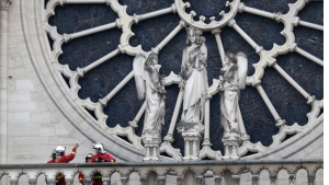 Firefighters talk near the rose window of Notre Dame cathedral Tuesday April 16, 2019 in Paris. (AP Photo/Thibault Camus)