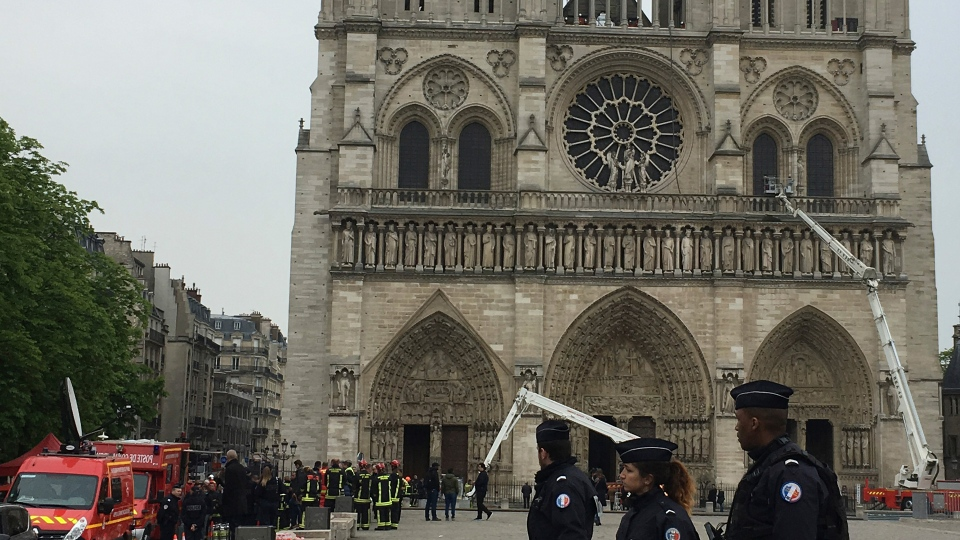 Police officers walk in front of Notre Dame cathedral Tuesday April 16, 2019 in Paris. Experts assessed the blackened shell of Paris' iconic Notre Dame Tuesday morning to establish next steps to save what remains after a devastating fire destroyed much of the cathedral that had survived almost 900 years of history. (AP Photo/Samuel Petrequin)