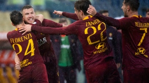 Roma's Edin Dzeko, left, celebrates afters scoring during the Serie a soccer match between Roma and Udinese at the Olympic Stadium in Rome, Saturday, April 13, 2019. (Claudio Peri/ANSA via AP)