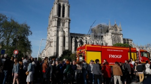 "People pass by the Notre Dame Cathedral in Paris, Wednesday, April 17, 2019. Notre Dame Cathedral would have been completely burned to the ground in a ""chain reaction collapse"" had firefighters not moved rapidly in deploying their equipment to battle the blaze racing through the landmark monument, a Paris official said Wednesday. (AP Photo/Michel Euler)"