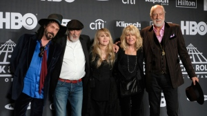 This March 29, 2019 file photo shows Inductee Stevie Nicks, center, posing with other members of Fleetwood Mac, from left, Mike Campbell, John McVie, Christine McVie and Mick Fleetwood at the Rock & Roll Hall of Fame induction ceremony in New York. Fleetwood Mac has announced rescheduled dates for its North America tour which were postponed earlier this month because singer Stevie Nicks had the flu. The Grammy-winning band is set to play Boston on Oct. 28 and Philadelphia on Nov. 3. Canadian dates include Quebec City on Oct. 30, Toronto and Nov. 1, Winnipeg of Nov. 7, Calgary on Nov. 10 and Edmonton on Nov. 30.  (Photo by Charles Sykes/Invision/AP, File)