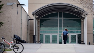 """A police officer walks to the front doors of Columbine High School, Wednesday, April 17, 2019, in Littleton, Colo., where two student killed 12 classmates and a teacher in 1999. The school was closed along with hundreds of others in Colorado after an armed young Florida woman who was allegedly """"infatuated"""" with Columbine threatened violence just days ahead of the 20th anniversary of the attack. (AP Photo/Joe Mahoney)"""