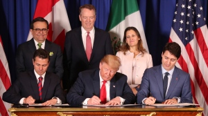 FILE - In this Nov. 30, 2018 file photo, President Donald Trump, center, sits between Canada's Prime Minister Justin Trudeau, right, and Mexico's President Enrique Pena Nieto as they sign a new United States-Mexico-Canada Agreement that is replacing the NAFTA trade deal, during a ceremony at a hotel before the start of the G20 summit in Buenos Aires, Argentina.  (AP Photo/Martin Mejia, File)