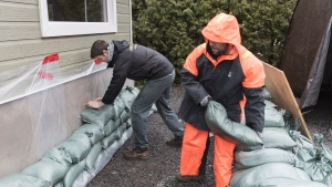Two men place sandbags next to the foundation of a house in the town of Rigaud, Que. west of Montreal, Friday, April 19, 2019. THE CANADIAN PRESS/Graham Hughes