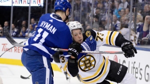 Boston Bruins defenceman Charlie McAvoy (73) gets tied up by Toronto Maple Leafs left wing Zach Hyman (11) during first period NHL playoff hockey action in Toronto on Sunday, April 21, 2019. THE CANADIAN PRESS/Nathan Denette