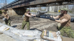 Canadian Forces personnel reinforce a dike against the rising flood waters in Laval, Que., on Sunday, April 21, 2019. THE CANADIAN PRESS/Ryan Remiorz