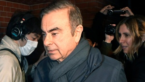 In this April 3, 2019, photo, former Nissan Chairman Carlos Ghosn, center, returns to his residence in Tokyo. Japanese prosecutors said Monday, April 22, 2019, they have indicted Nissan's former chairman Ghosn with additional charges of breach of trust, with his alleged misconduct expanding outside Japan. (Mizuki Ikari/Kyodo News via AP)