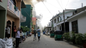 Smoke rises after a vehicle parked near St. Anthony's shrine exploded in Colombo, Sri Lanka, Monday, April 22, 2019. Easter Sunday bombings that ripped through churches and luxury hotels killed more than 200 people. (AP Photo/Eranga Jayawardena)