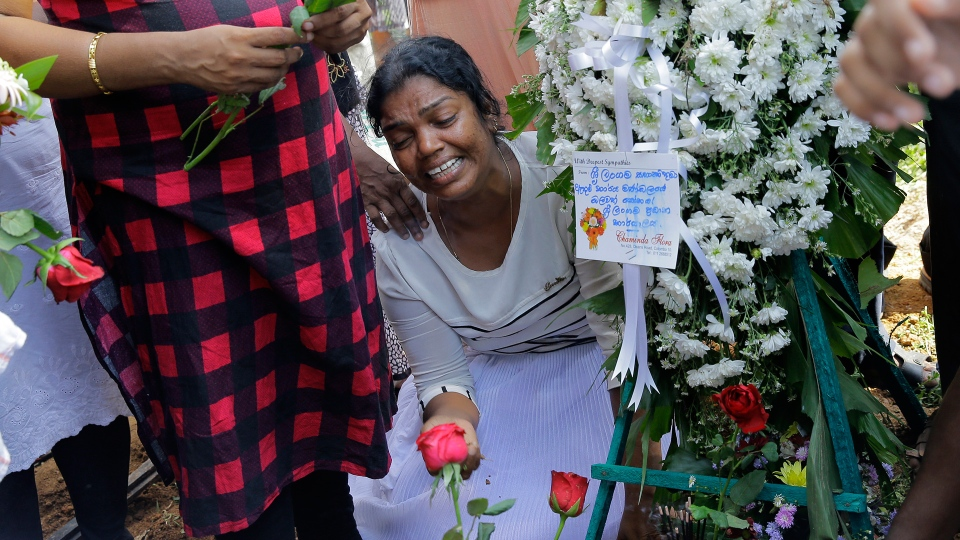 Wasanthi, a member of Berlington family weeps over the gave of Bevon, who was killed in the Easter Sunday bombings in Colombo, Sri Lanka, Tuesday, April 23, 2019. (AP Photo/Eranga Jayawardena)