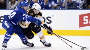 Toronto Maple Leafs defenceman Morgan Rielly (44) and Boston Bruins left wing Jake DeBrusk (74) battle for the puck during third period NHL playoff hockey action in Toronto on Sunday, April 21, 2019. THE CANADIAN PRESS/Nathan Denette