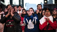 People watch the NBA Toronto Raptors and the NHL Maple Leafs on large outdoor screens in Maple Leaf Square in Toronto on Tuesday, April 23, 2019. and THE CANADIAN PRESS/Christopher Katsarov