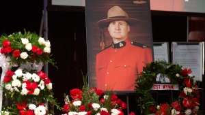A photo of slain RCMP Constable David Wynn stands amongst flowers during his funeral procession in St. Albert, Alta., on January 26, 2015. THE CANADIAN PRESS/Jason Franson