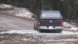 A car makes its way through a flooded road in Bracebridge, Ont.