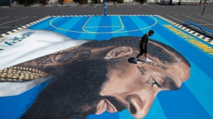 In this April 17, 2019 photo, mural artist Gustavo Zermeno Jr. walks on a basketball court mural he dedicated to slain rapper Nipsey Hussle in Los Angeles. More than 50 colorful murals of Hussle have popped up in Los Angeles since the beloved rapper and community activist was gunned down outside his clothing store. (AP Photo/Jae C. Hong)