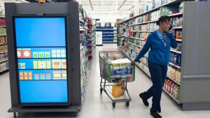 A customer pulls her shopping cart past an information kiosk at a Walmart Neighborhood Market, Wednesday, April 24, 2019, in Levittown, N.Y. Kiosks and signs throughout the store keep customers informed that they are shopping in an artificial intelligence factory. (AP Photo/Mark Lennihan)