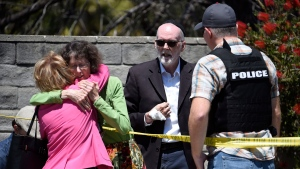 Two people hug as another talks to a San Diego County Sheriff's deputy outside of the Chabad of Poway Synagogue Saturday, April 27, 2019, in Poway, Calif. (AP / Denis Poroy)