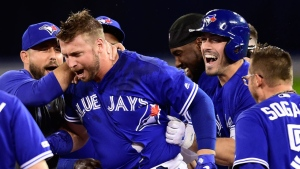 Toronto Blue Jays first baseman Justin Smoak (second left) is mobbed by temmates after driving in the game-winning run against the Oakland Athletics during 11th inning American League baseball action in Toronto on Sunday, April 28, 2019. THE CANADIAN PRESS/Frank Gunn