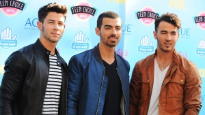 In this Aug. 11, 2013 file photo, from left, Nick Jonas, Joe Jonas and Kevin Jonas of the musical group Jonas Brothers arrive at the Teen Choice Awards at the Gibson Amphitheater, in Los Angeles. The Jonas Brothers are canceling their tour two days before it begins on Oct. 11, 2013. (Photo by Jordan Strauss/Invision/AP, File)