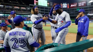 Toronto Blue Jays manager Charlie Montoyo (25), player Vladimir Guerrero Jr., center left, and others celebrate with Socrates Brito, center right, who scored on an Eric Sogard triple during the fourth inning of a baseball game against the Texas Rangers in Arlington, Texas, Saturday, May 4, 2019. (AP Photo/Tony Gutierrez)