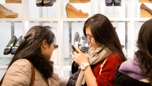 A customer uses her cell phone in the shoe section of the Macy's Herald Square flagship store, Thursday, Nov. 28, 2013, in New York. (AP Photo/John Minchillo)
