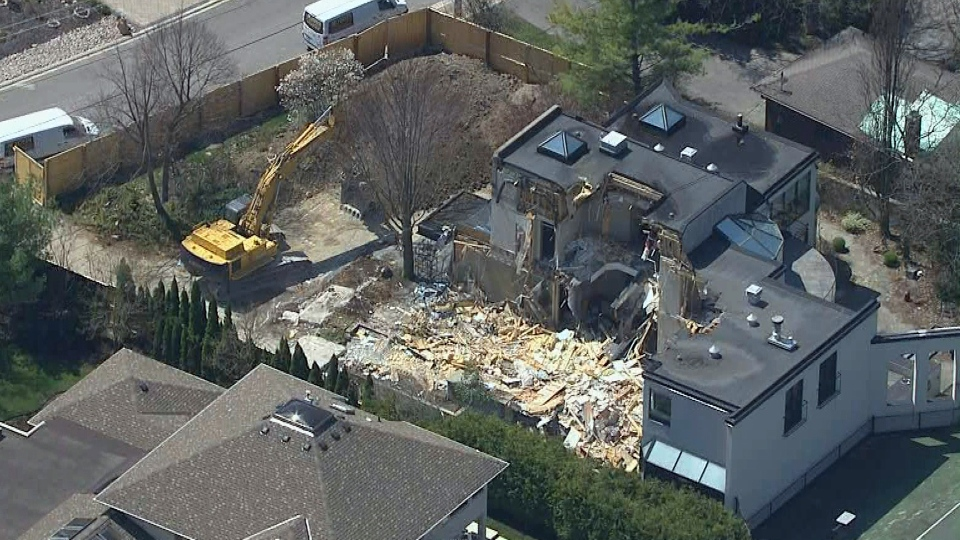 A bulldozer tears down the home of Honey and Barry Sherman at 50 Old Colony Road Monday May 6, 2019.