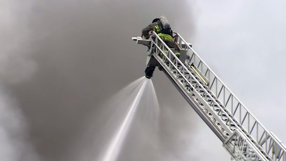 A firefighter aims water from an aerial ladder at a six-alarm fire at York Memorial Collegiate Institute Tuesday May 7, 2019.