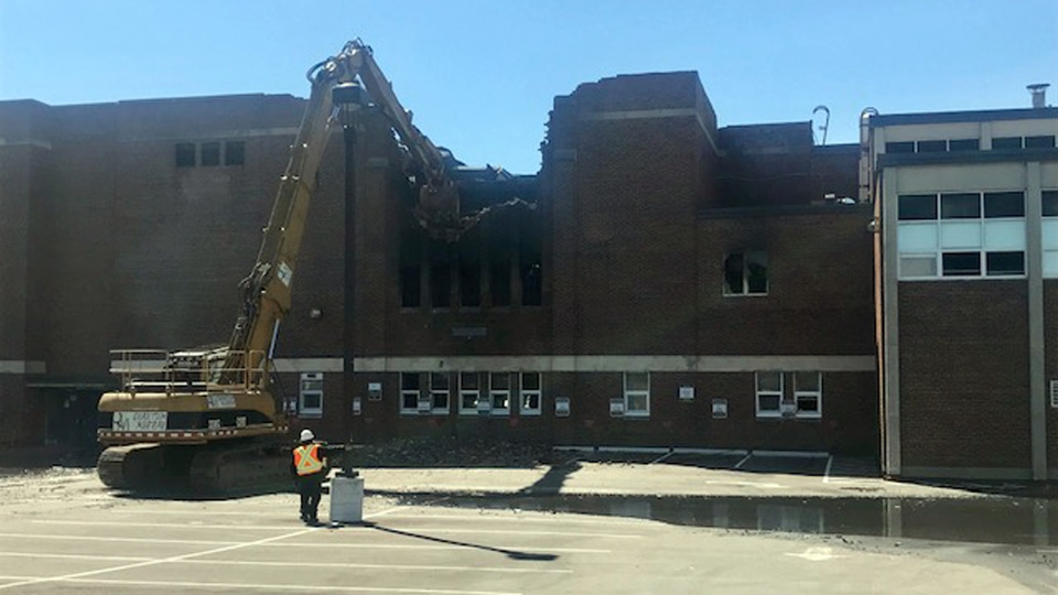 Fire crews use heavy equipment to get at the remains of a stubborn fire at York Memorial Collegiate Institute Wednesday May 8, 2019. (Cristina Tenaglia /CP24)