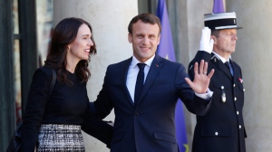 New Zealand Prime Minister Jacinda Ardern, left, is greeted by French President Emmanuel Macron, center, as she arrives at the Elysee Palace, in Paris, Wednesday, May 15, 2019. World leaders and tech bosses meet Wednesday in Paris to discuss ways to prevent social media from spreading deadly ideas. (AP Photo/Francois Mori)
