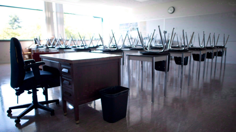 Am empty teacher's desk is pictured at the front of a empty classroom at Mcgee Secondary school in Vancouver on Sept. 5, 2014. (Jonathan Hayward/The Canadian Press)
