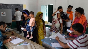 Election officers check the identity of voters before allowing them to cast their votes during the seventh and final phase of national elections, on the outskirts of Varanasi, India, Sunday, May 19, 2019. (AP Photo/Rajesh Kumar Singh)