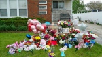 A memorial of flowers, balloons, a cross and photo of victim Marlen Ochoa-Lopez, are displayed on the lawn, Friday, May 17, 2019 in Chicago, outside the home where Ochoa-Lopez was murdered last month. (AP Photo/Teresa Crawford)