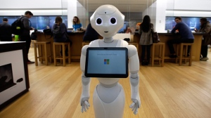 "In this March 21, 2019 photo a robot called ""Pepper"" is positioned near an entrance to a Microsoft Store location, in Boston. (AP Photo/Steven Senne, File)"