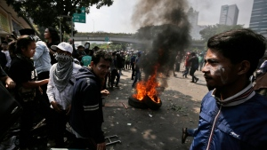 Protesters rest near burning tires during a clash with the police in Jakarta, Indonesia, Wednesday, May 22, 2019. Supporters of an unsuccessful presidential candidate clashed with security forces in the Indonesian capital on Wednesday, burning vehicles and throwing rocks at police using tear gas and rubber bullets. (AP Photo/Dita Alangkara)