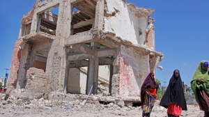 Somali women walk past a destroyed building after a suicide car bomb attack in the capital Mogadishu, Somalia Wednesday, May 22, 2019. A police spokesman said the attack killed at least six people and injured more than a dozen, while Islamic extremist group al-Shabab claimed responsibility for the blast, saying it targeted vehicles carrying government officials. (AP Photo/Farah Abdi Warsameh)