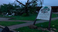 The sign for the Hidden Oaks apartment complex in Jefferson City Missouri stands bent Thursday, May 23, 2019, from a tornado in front of a tree that was ripped apart. The National Weather Service has confirmed a large and destructive tornado has touched down in Missouri's state capital, causing heavy damage and trapping multiple people in the wreckage of their homes. (AP Photo/David A. Lieb)