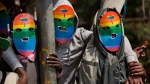 In this Monday, Feb. 10, 2014 file photo, Kenyan gays and lesbians and others supporting their cause wear masks to preserve their anonymity as they stage a rare protest, against Uganda's increasingly tough stance against homosexuality and in solidarity with their counterparts there, outside the Uganda High Commission in Nairobi, Kenya. Kenya's High Court is due to rule Friday, May 24, 2019 on whether laws that criminalize same sex relations in Kenya are unconstitutional. (AP Photo/Ben Curtis, File)