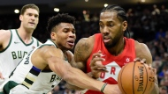 Milwaukee Bucks forward Giannis Antetokounmpo (34) defends as Toronto Raptors forward Kawhi Leonard (2) controls the ball during second half action in Game 5 of the NBA Eastern Conference final in Milwaukee on Thursday, May 23, 2019. THE CANADIAN PRESS/Frank Gunn
