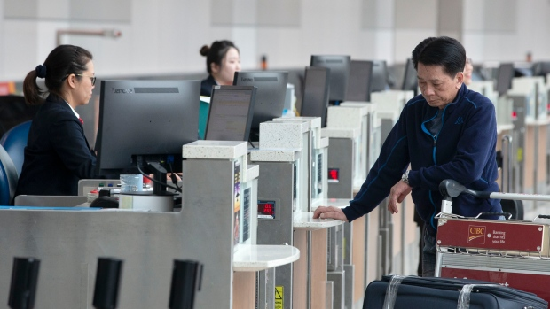 A passenger checks in for a flight at Toronto Pearson Airport, in Mississauga, Ont., Friday, May 24, 2019. New regulations requiring airlines to provide help and compensation to passengers stuck on a tarmac for hours will kick in on July 15. THE CANADIAN PRESS/Chris Young
