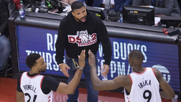 Toronto Raptors forward Norman Powell (24) and Raptors centre Serge Ibaka (9) celebrate with Drake, centre, while playing giants the Milwaukee Bucks during second half NBA Eastern Conference finals basketball action in Toronto on Tuesday,May 21, 2019. THE CANADIAN PRESS/Nathan Denette