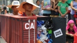In this May 7, 2015, file photo, Filipino environmental activists wear a mock container vans filled with garbage to symbolize the 50 containers of waste that were shipped from Canada to the Philippines two years ago, as they hold a protest outside the Canadian embassy at the financial district of Makati, south of Manila, Philippines. (AP Photo/Aaron Favila, File)