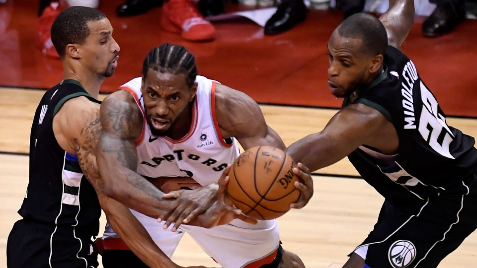 Toronto Raptors forward Kawhi Leonard (2) gets bound up by Milwaukee Bucks guard George Hill (3) and teammate Khris Middleton (22) during second half NBA Eastern Conference finals action in Toronto on Saturday, May 25, 2019. THE CANADIAN PRESS/Frank Gunn