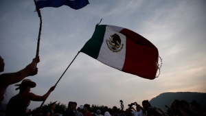 "Migrants wave the flags of Honduras and Mexico as they stand stalled after Mexican police blockaded the road to keep them from advancing, outside the town of Arriaga, Chiapas State, Mexico on October 27, 2018. The United Nations is urging Canada to help ease Mexico's refugee burden by helping resettle some of the most vulnerable of its new arrivals, including women, children and LGBTQ people. Mexico is feeling the squeeze from an unprecedented exodus of people fleeing Central American countries and some of the worst violence from nations not at actually war is forcing families northward. ""Our pitch to Canada is to do more,"" said Mark Manly, the Mexico representative of the United Nations High Commissioner for Refugees. THE CANADIAN PRESS/AP, Rebecca Blackwell"