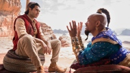 """This image released by Disney shows Mena Massoud as Aladdin, left, and Will Smith as Genie in Disney's live-action adaptation of the 1992 animated classic """"Aladdin."""" (Daniel Smith/Disney via AP)"""