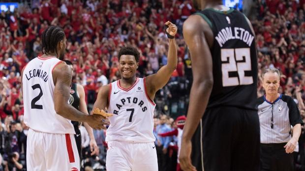 6d5947b16bb Toronto Raptors guard Kyle Lowry (7) reacts with teammate Kawhi Leonard (2)  as Milwaukee Bucks forward Khris Middleton (22) looks on during the final  ...