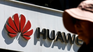 A woman walks by a Huawei retail store in Beijing, Wednesday, May 29, 2019. (AP Photo/Andy Wong)