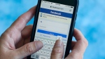 "Facebook is reportedly in talks with news publishers to offer ""millions of dollars"" for the rights to publish their material on its site. In this Aug. 21, 2018 file photo, a Facebook start page is shown on a smartphone in Surfside, Fla. (AP Photo/Wilfredo Lee, File)"