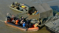 South Korean and Hungarian divers work on a floating pier at Margaret Bridge, at the site of the accident involving South Korean tourists, in Budapest, Hungary, Saturday, June 1, 2019. On Wednesday, May 29, 2019 a hotelship and a sightseeing ship collided on the River Danube in downtown Budapest, and the latter sank with thirty-three South Korean passengers and two Hungarian staff on board. (Lajos Soos/MTI via AP)